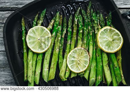 Grilled Asparagus. Baked Or Grilled Green Asparagus With Lemon In Black Cast Iron Pan, Top View