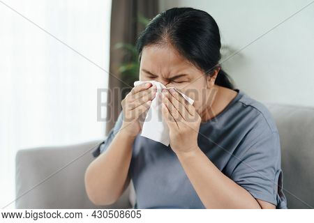 Cold Sick Woman Got Nose Allergy Cough Or Sneeze With Tissue Paper Sitting On The Sofa. Healthcare A