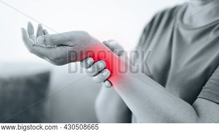 Closeup Of Woman Sitting On Sofa Holds Her Wrist, Hand Injury With Red Highlight, Feeling Pain. Heal