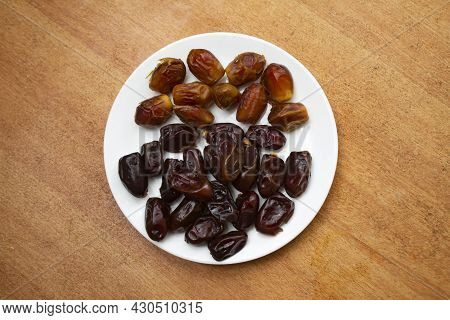 Dried Dates On Wooden Background. Premium Quality Date Fruit Isolated On A Plate. Date Fruit With Wo