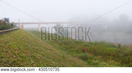 Landscape With Sava River, Promenade On Riverbank Embankment And Concrete Bridge Over The River Duri