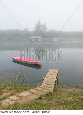 Landscape With Sava River Fishing Huts And Moored Boat Near Riverbank During Misty Autumn Morning