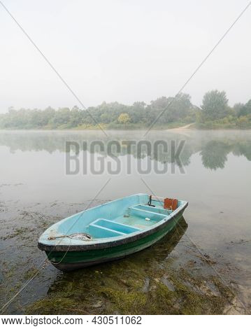 Landscape Of Sava River In Autumn, Moored Green And Blue Boat In Shallow Water Surrounded With Algae
