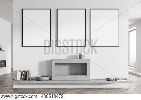 Living Room Interior With Three Posters On White Wall Partition And Grey Fireplace With Shelf Below.