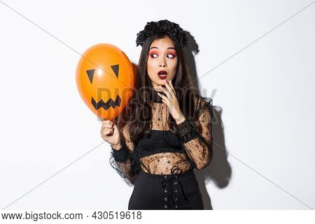 Portrait Of Girl Looking Scared At Orange Balloon With Creepy Face, Wearing Witch Costume, Celebrati