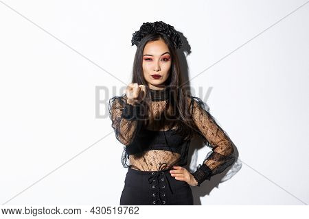 Sassy Elegant Young Asian Woman In Witch Halloween Costume Tell Come Closer, Flicking Finger As Lure