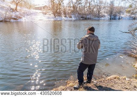A Fisherman With A Fishing Rod Catches Fish On The Banks Of A Snow-covered River In Early Spring.