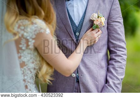 Bride's Hands Pinning A Small Boutonniere To A Jacket For The Groom. Floral Traditional Decoration F
