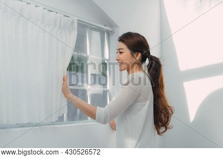 Young Woman Standing In Front Of The Bedroom Window Looking Outside