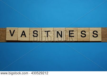 Gray Word Vastness In Small Square Wooden Letters With Black Font On A Blue Background