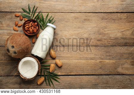 Delicious Vegan Milk, Almonds And Coconuts On Wooden Table, Flat Lay. Space For Text