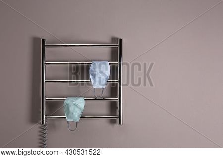 Modern Heated Towel Rail With Cloth Face Masks On Grey Wall. Space For Text