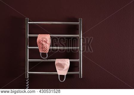 Modern Heated Towel Rail With Cloth Face Masks On Dark Wall. Space For Text