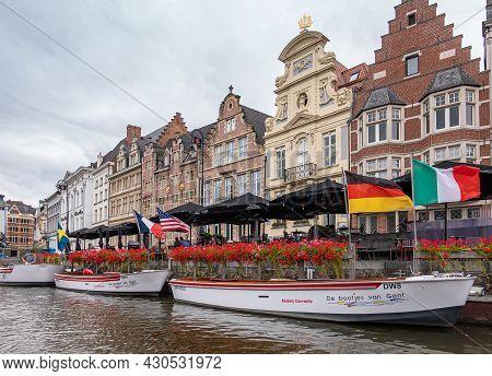 Gent, Flanders, Belgium - July 30, 2021: Tourist Tour Boats On Leie River Docked At Korenlei Showing