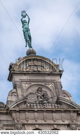Gent, Flanders, Belgium - July 30, 2021: Green Bronze Statue On Top Of Nyg Theater Building Gable Ag