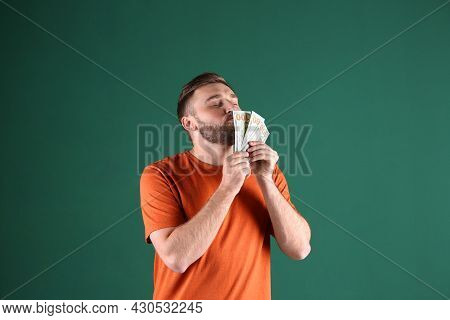 Greedy Young Man Sniffing Money On Green Background