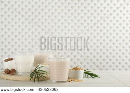 Different Vegan Milks And Ingredients On White Wooden Table. Space For Text