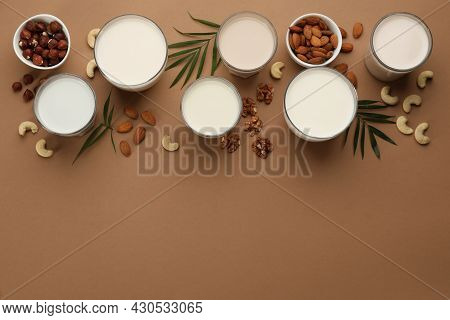 Different Vegan Milks And Nuts On Brown Background, Flat Lay. Space For Text