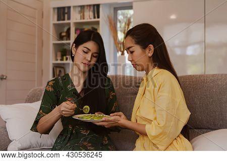 Portrait Two Beautiful Asian Women Ate In-house Chopped Fresh Kiwi Fruit As A Snack, Eating Healthy