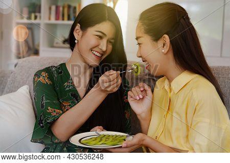 Smile Portrait Two Beautiful Asian Women Ate In-house Chopped Fresh Kiwi Fruit As A Snack, Eating He