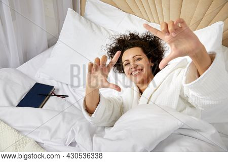 Smiling Woman Waking Up In Bed And Stretching Her Arms Up Making Picture Frame With Hands Pretnding
