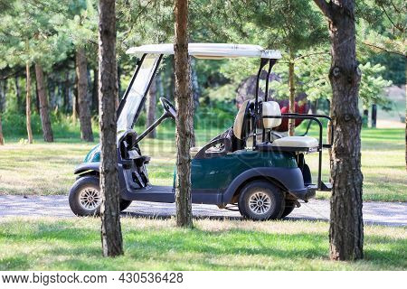Belarus. Minsk - 24.07.2021 The Electric Car On The Golf Course Stands In The Shade Of The Trees.