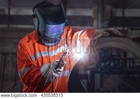 Industrial Worker With Protective Mask Welding Metal Pipe In A Factory