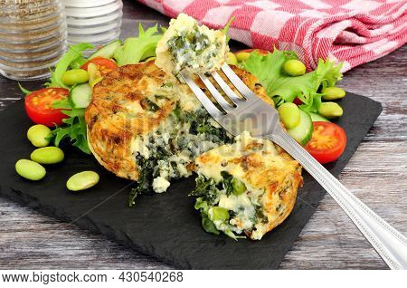 Spinach And Kale Quiche With Fresh Salad And Edamame Beans On A Slate Serving Board
