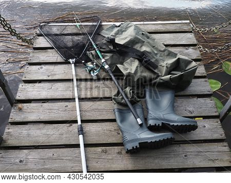 Chest Waders, Fish Catch Net And Fishing Rod. Hobby And Spending Time In Nature.