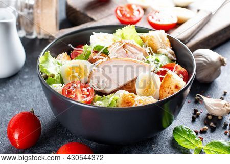 A Delicious Chicken Caesar Salad With Parmesan Cheese, Dressing And Croutons On A Dark Background