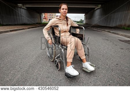 A Young Disabled Girl Sits In A Wheelchair On The Street. The Concept Of A Wheelchair, Disabled Pers
