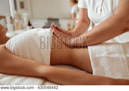 Masseuse Hands Massaging Woman Abdomen At Wellness Center