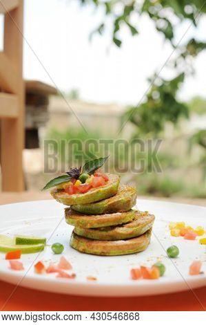 Vegetable fritters of zucchini served on a plate, outdoor cafe