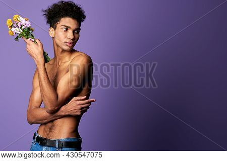Portrait Of Latino Transgender Male Model With Bouquet On Purple Background. Young Man Nacked Torso