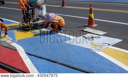 Road Workers Group With Thermoplastic Spray Road Marking Machine Are Working To Paint Traffic Sign A