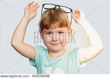 An Attractive Funny Little Girl Holds Black Glasses Over Her Head On A Light Background. Funny Blond
