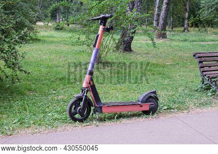 Abandoned Electric Scooter Near The Path In A City Park. Discharged Electric Scooter Battery. City E