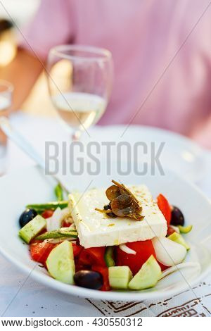 Delicious Greek salad with fresh vegetables and Greek goat feta cheese served with white wine for lunch in restaurant