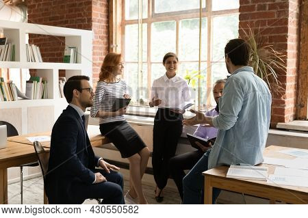 Five Employees Gather In Morning Briefing Led By Caucasian Executive