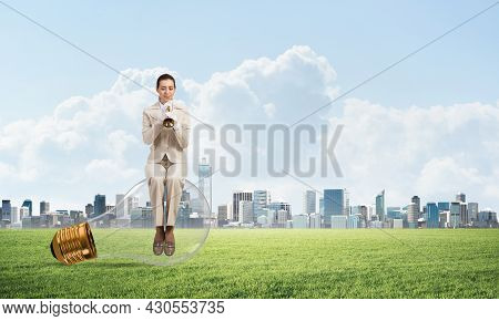 Attractive Woman Playing Trumpet Brass On Green Grass. Young Businesslady In White Suit Sitting On B