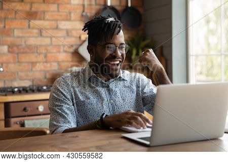 Excited African Millennial Guy Using Laptop At Home