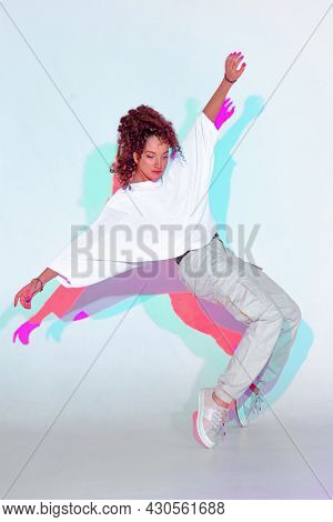 Dancing Mixed Race Young Girl In Colourful Light. Female Dancer Showing Contemporary Hip Hop Dance S