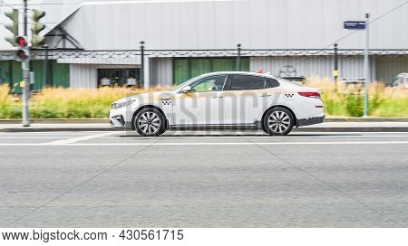 Taxi Car Toyota Camry Speeding On City Road. White Taxi Car Fast Moving On The Street. Side View Of