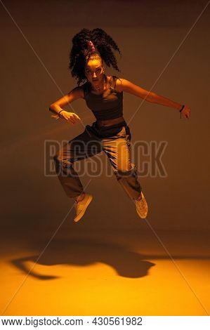 Dancing Mixed Race Girl Jumping And Levitating In Warm Studio Light. Female Dancer Performer Jump In