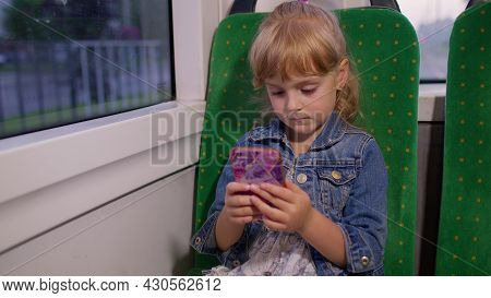 Little Girl Playing On Smartphone, Chatting, Texting, Browsing Social Media While Traveling By Bus I