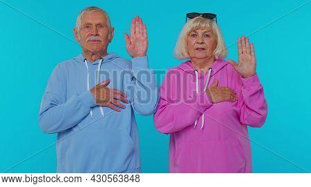 We Swear To Be Honest. Sincere Responsible Senior Couple Man Woman Grandparents Raising Hands To Tak