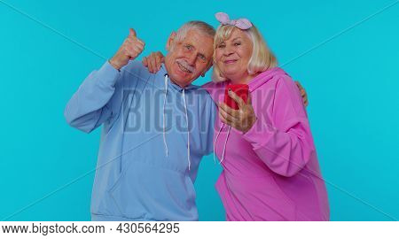 Excited Happy Joyful Senior Couple Man Woman Grandparents Use Mobile Cell Phone Typing Browsing Say