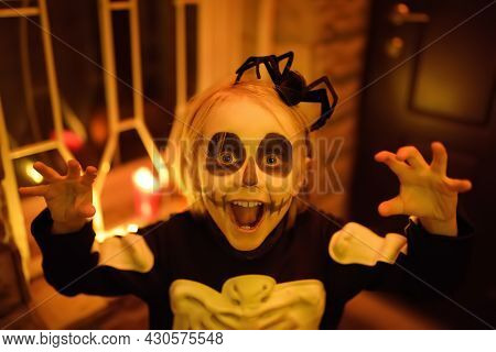 Little Child In Scary Skeleton Costume At Halloween Celebration Party. The Child Is Ready For Trick