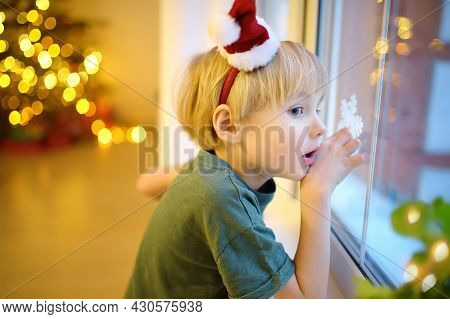 Little Excited Child Is Waiting Santa Claus On Christmas Eve. Preschooler Boy Looking On Window And