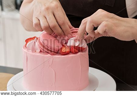 Woman Pastry Chef Decorates Pink Cake With Macaroons And Berries, Close-up. Cake Making Process, Sel